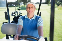 002_Happy golfer driving his golf buggy smiling at camera