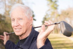 Active senior adult man playing golf